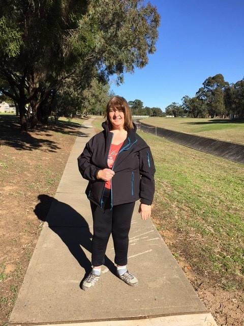 Suzie, a client of Active Ability with ID, standing on a footpath ready to do her walking program for physical and mental health.