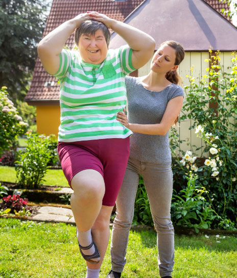 Woman with an intellectual disability being supported by an exercise physiologist as she balances on a mat with her hands on her head