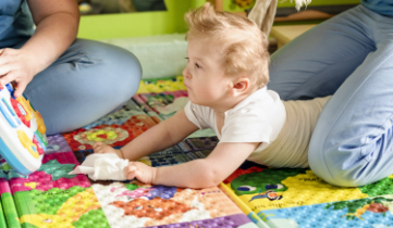 Image f a baby on the floor developing her gross and fine motor skills