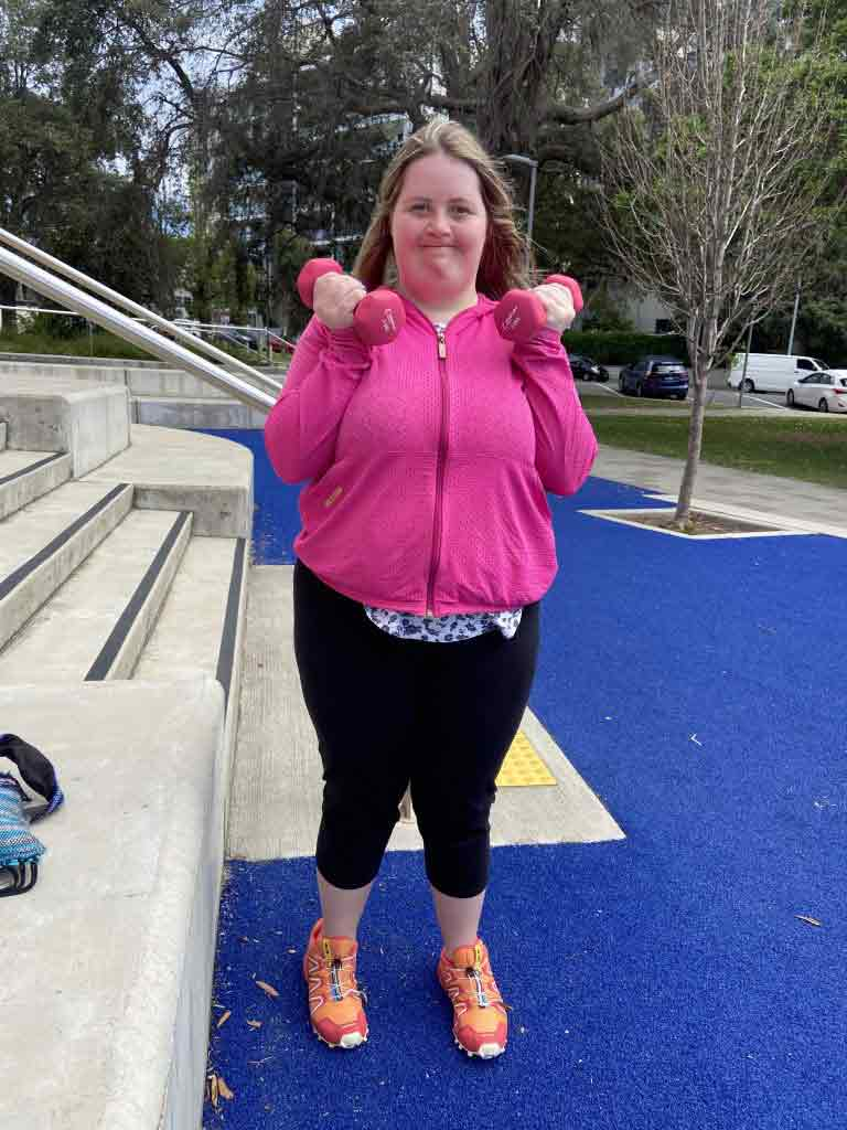 Woman standing in park in gym clothes performing a bicep curl with dumbbells