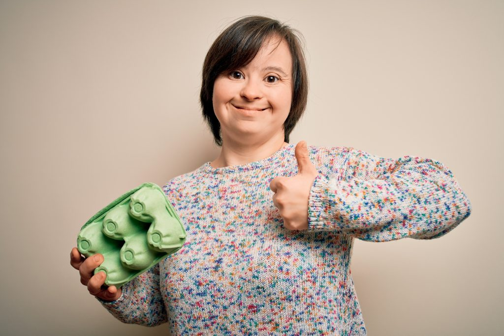 Image of a young woman with Down syndrome smiling, holding an egg carton and giving a thumbs up