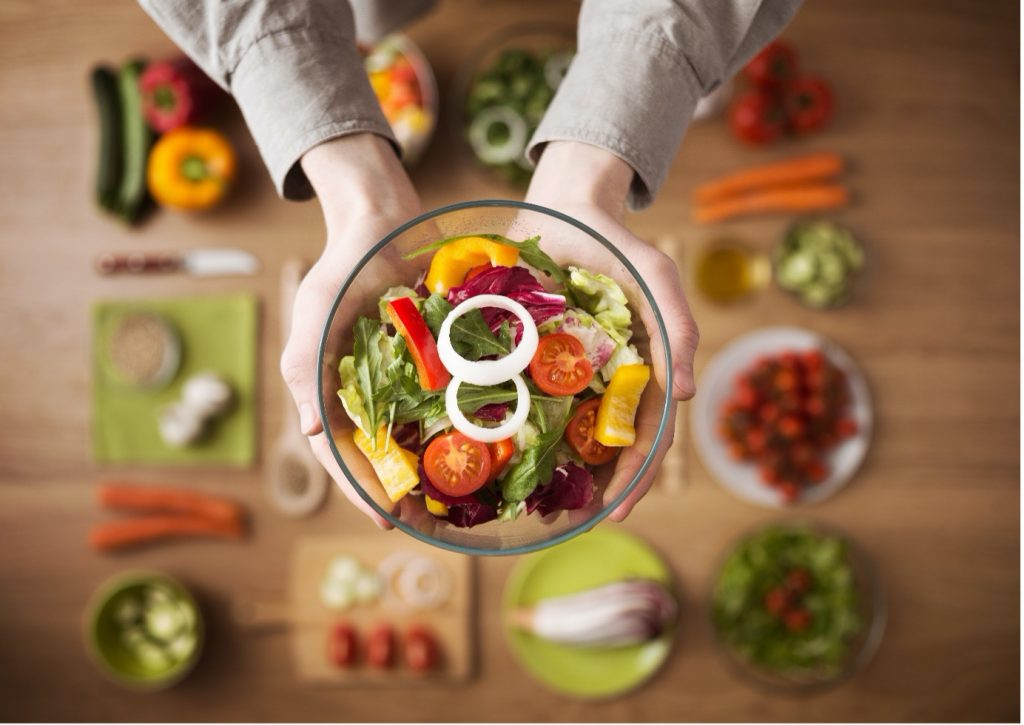 Image of someone holding up a bowl full of healthy salad