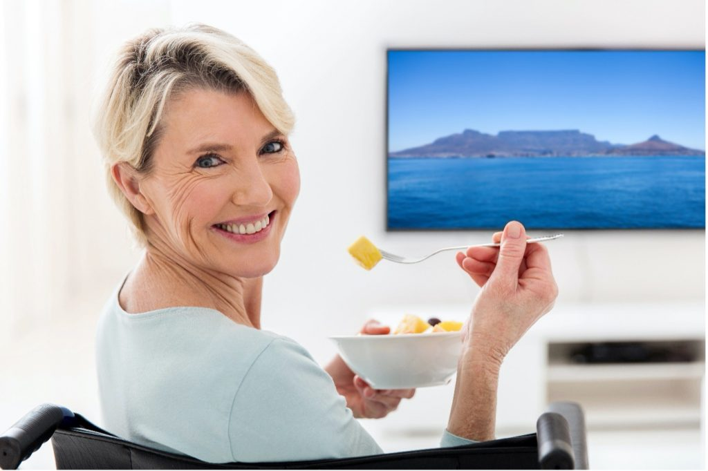 Image of a smiling woman in a wheelchair eating a bowl of healthy fruit salad